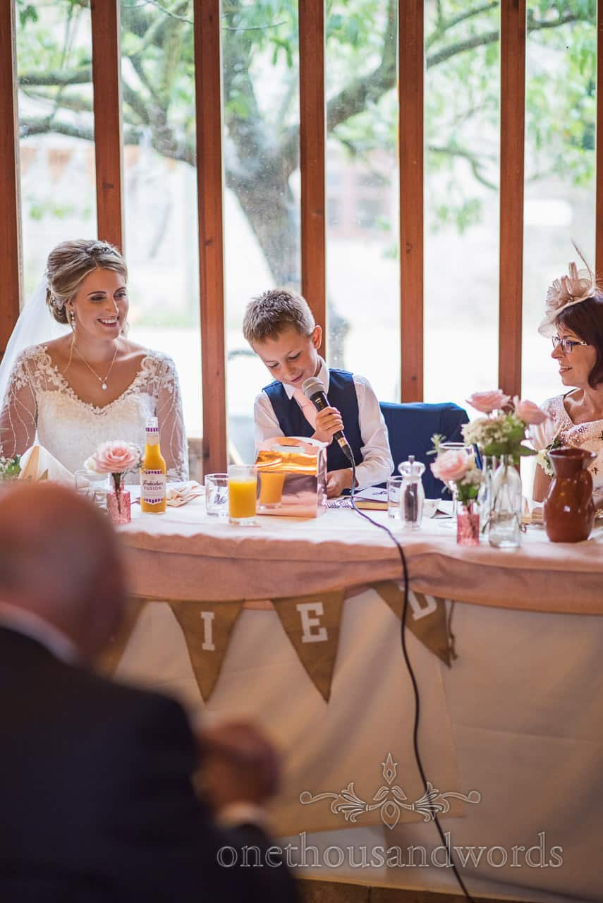 Bride's son delivers wedding speech using microphone at Kingston barn wedding photographs by one thousand words photography