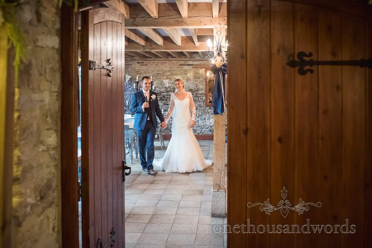 Documentary wedding photograph of bride and groom captured through wooden doorway at Kingston barn wedding venue