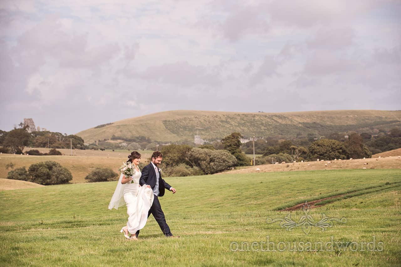 Bride and groom walk across field together in Purbeck, Dorset countryside wedding photographs by one thousand words photography