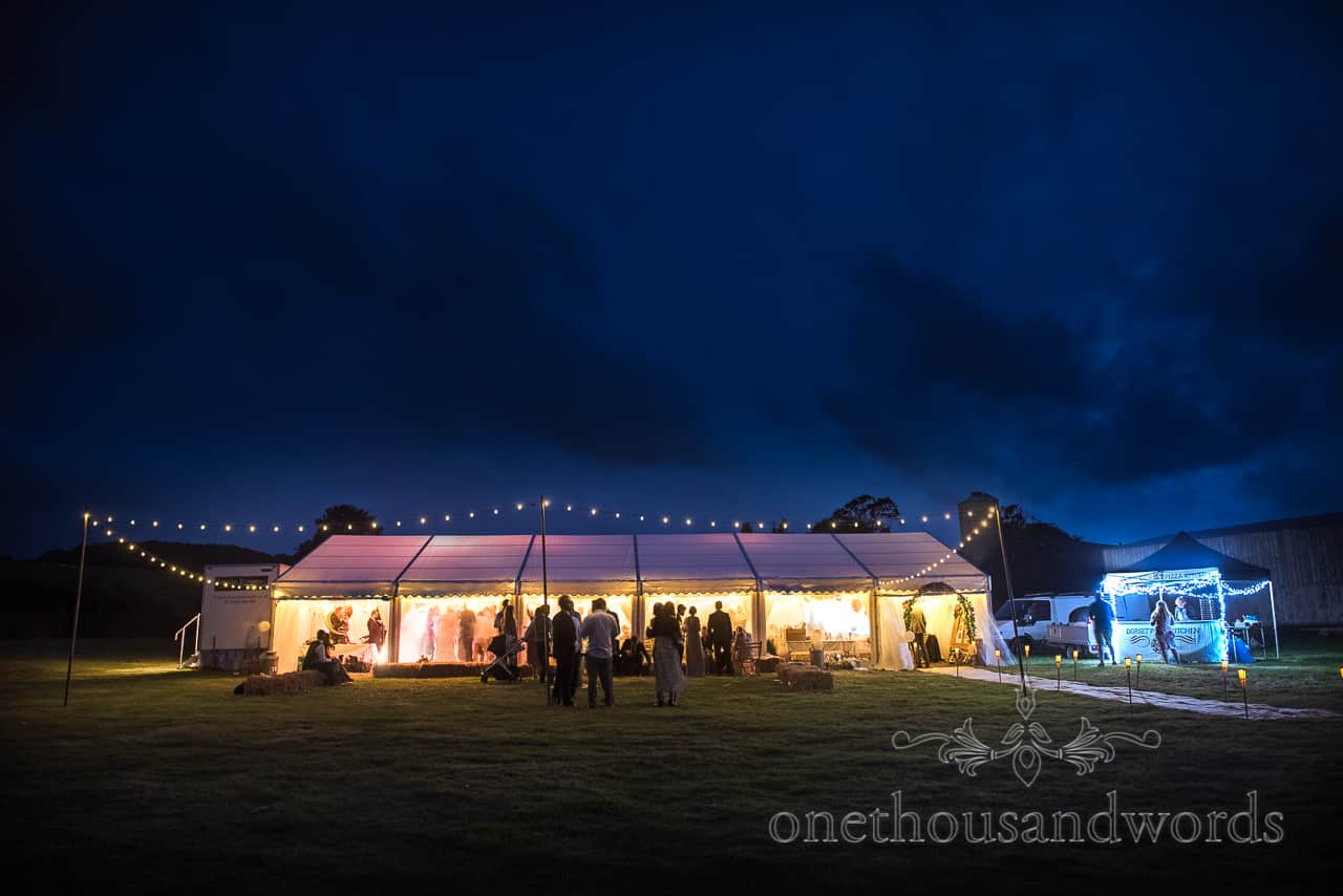 Night time wedding photograph of festoon lighting and glowing marquee from Purbeck farm marquee wedding photographs