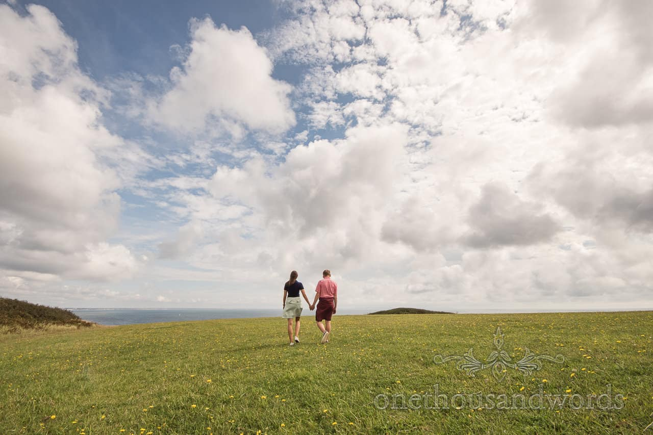 Old Harry Rocks engagement photograph of couple walking hand in hand though sea side field by one thousand words photography
