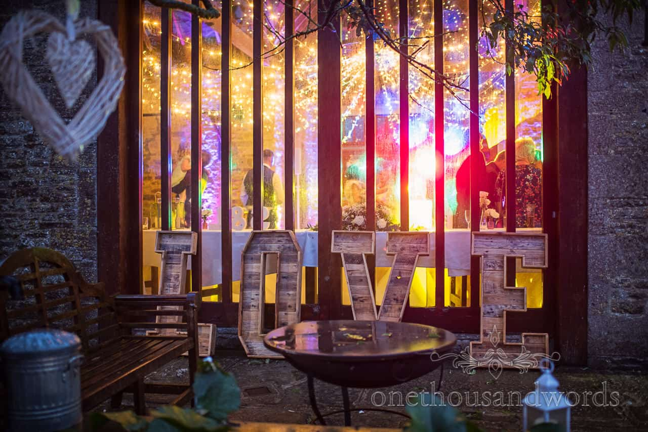 Giant LOVE letters photograph taken outside Kingston barn wedding venue at night during evening disco with multicoloured lighting