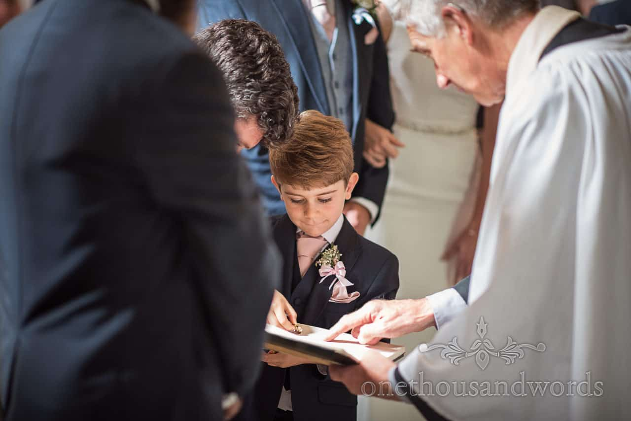 Page boy helps deliver wedding rings for vicars blessing during church wedding ceremony by documentary photographers in Dorset