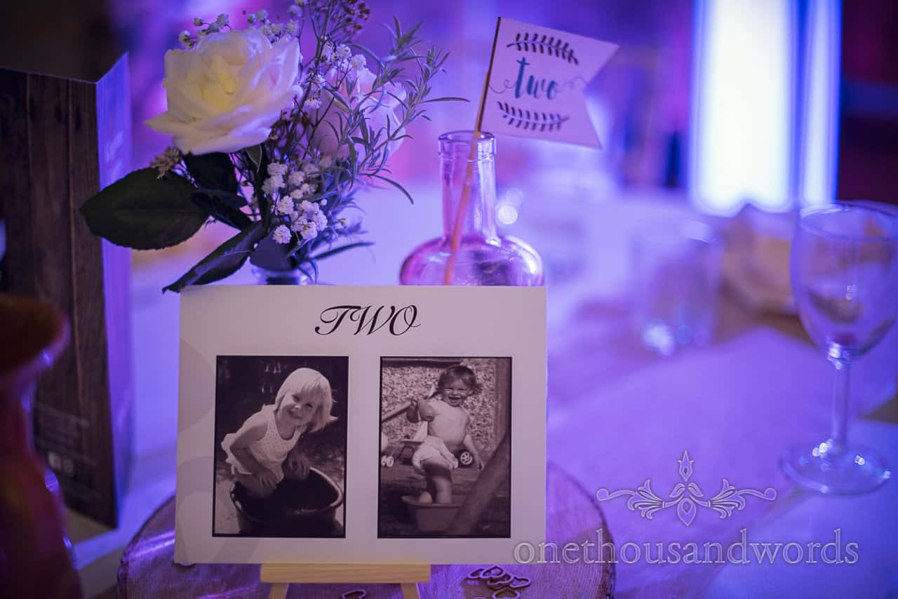 Wedding detail photograph under blue lighting of table number signage with bride and groom baby photographs