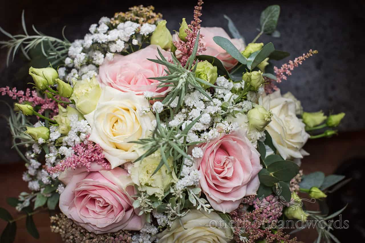 Pink and yellow roses with white Gypsophila and green foliage in bridal wedding bouquet detail photograph by one thousand words