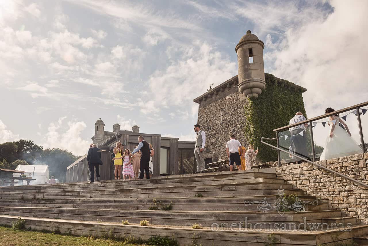 Purbeck castle summer wedding venue with barbecue and bride view from garden during drinks reception