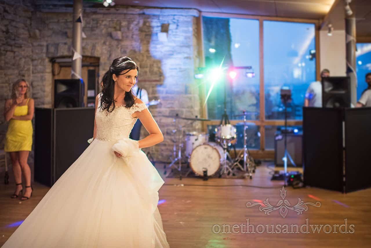 Purbeck castle wedding photographs of bride during first dance with disco lights by one thousand words wedding photography