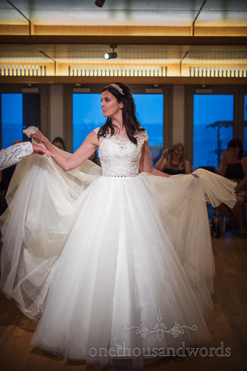 Bride poses with layers of wedding dress during first dance by the sea documentary photo by one thousand words wedding photography