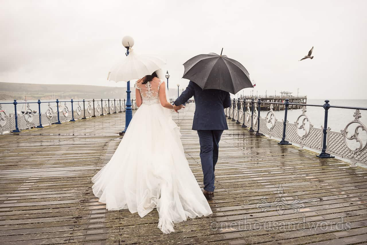 Bride and groom walk hand in hand along Swanage Victorian pier in Dorset under umbrellas in the rain with a sea gull
