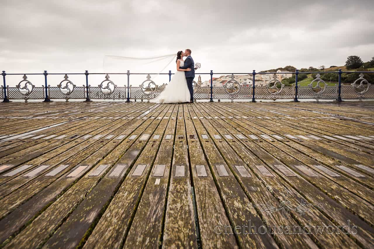 Bride and groom kiss with veil in the wind on Swanage Victorian pier photo by one thousand words wedding photographers in Dorset