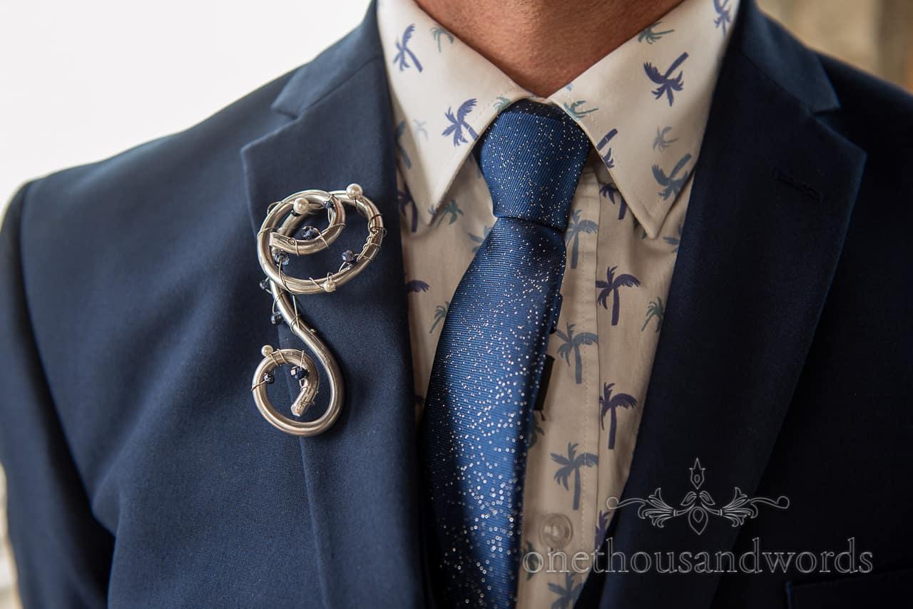 Refinerii Bridal metal buttonhole boutonnière with blue suit, blue sparkly wedding tie and palm tree print shirt