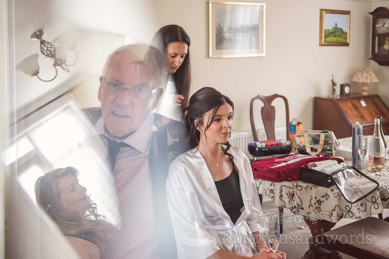 Reflections of bridesmaid and father watching bridal hair styling during wedding morning preparation photographs by one thousand words