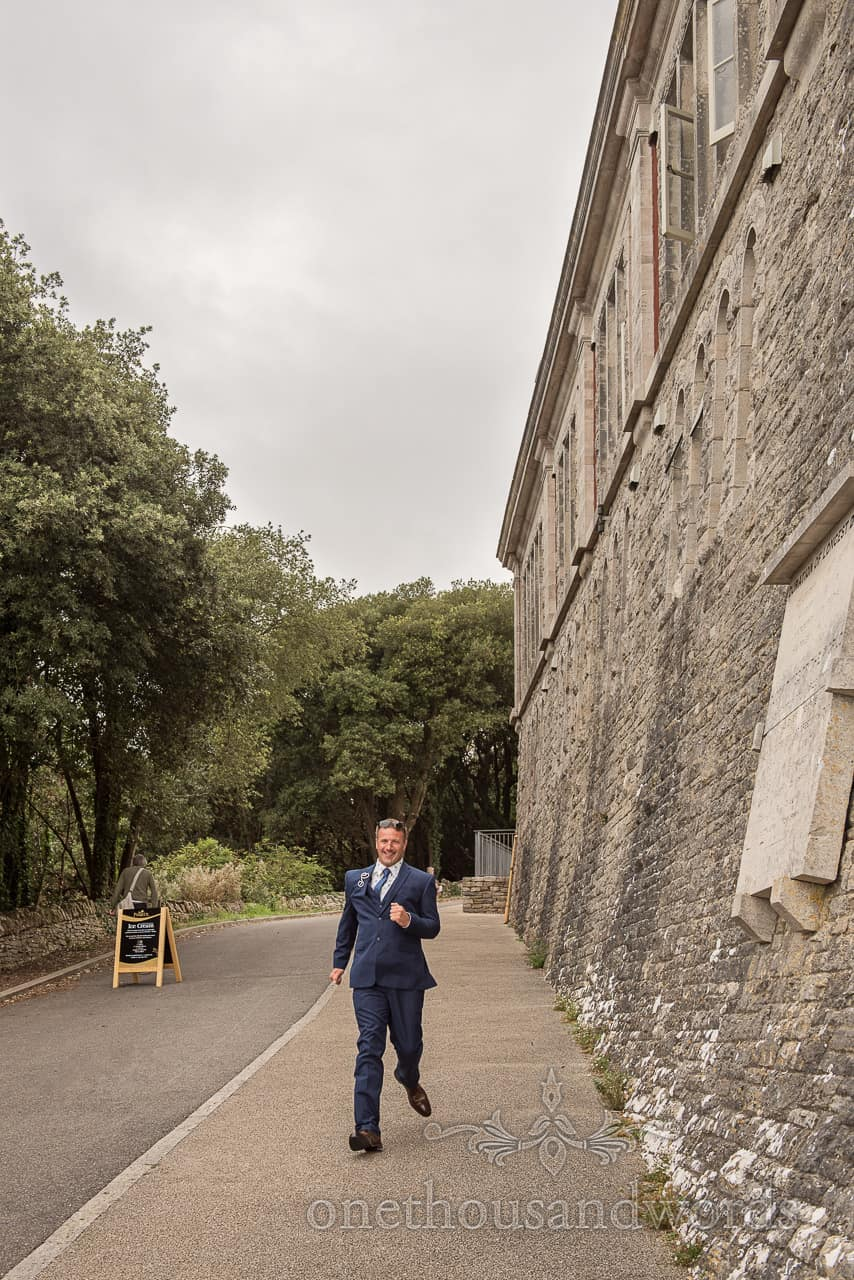 Happy groom in blue wedding suit runs alongside castle walls down path to Durlston Castle civil wedding ceremony in Dorset