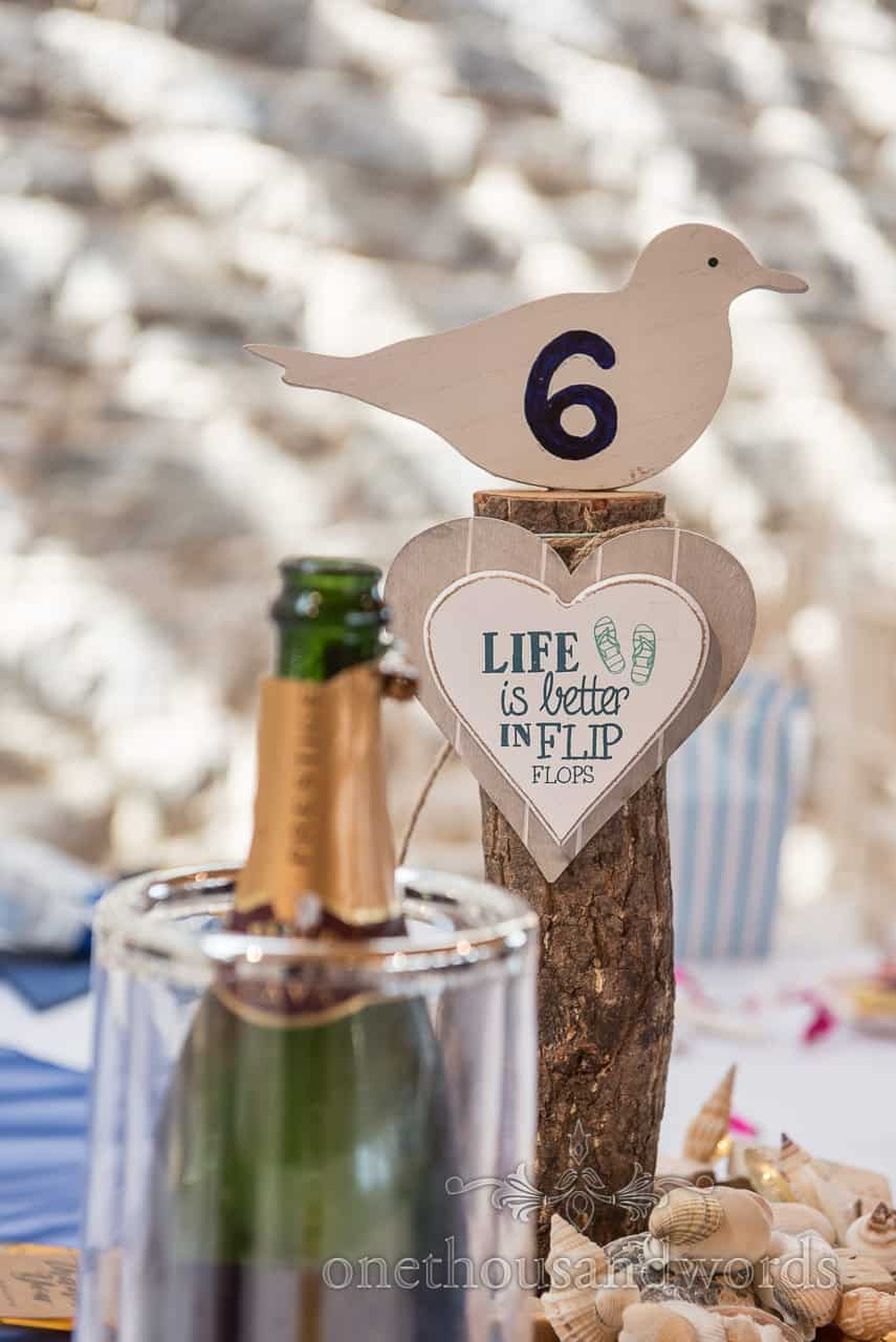 """Seagull wedding table number center piece on wooden log with love heart """"Life Is Better In Flip Flops"""" Sign and sea shells photograph"""