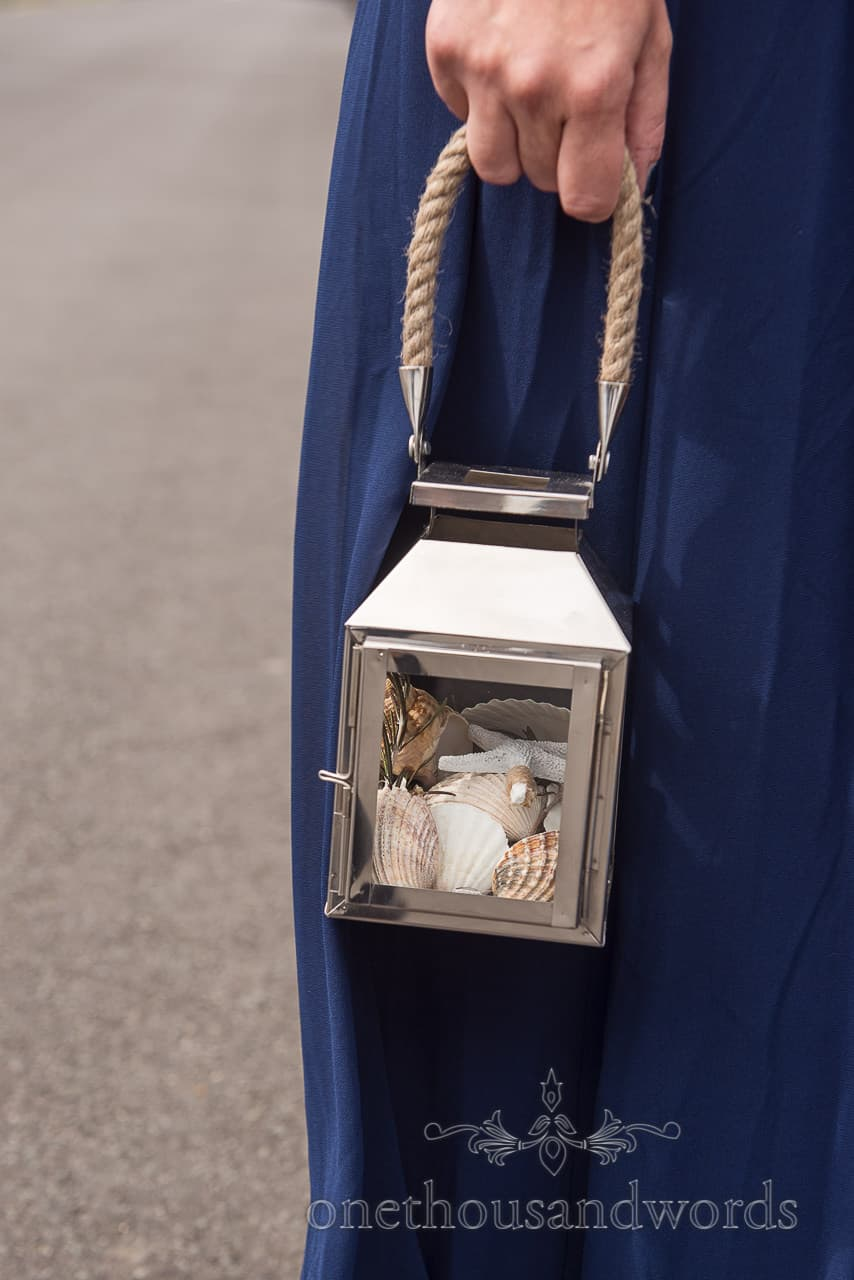 Bridesmaid's seashell lantern with rope handle against blue dress wedding detail photograph by one thousand words photographers
