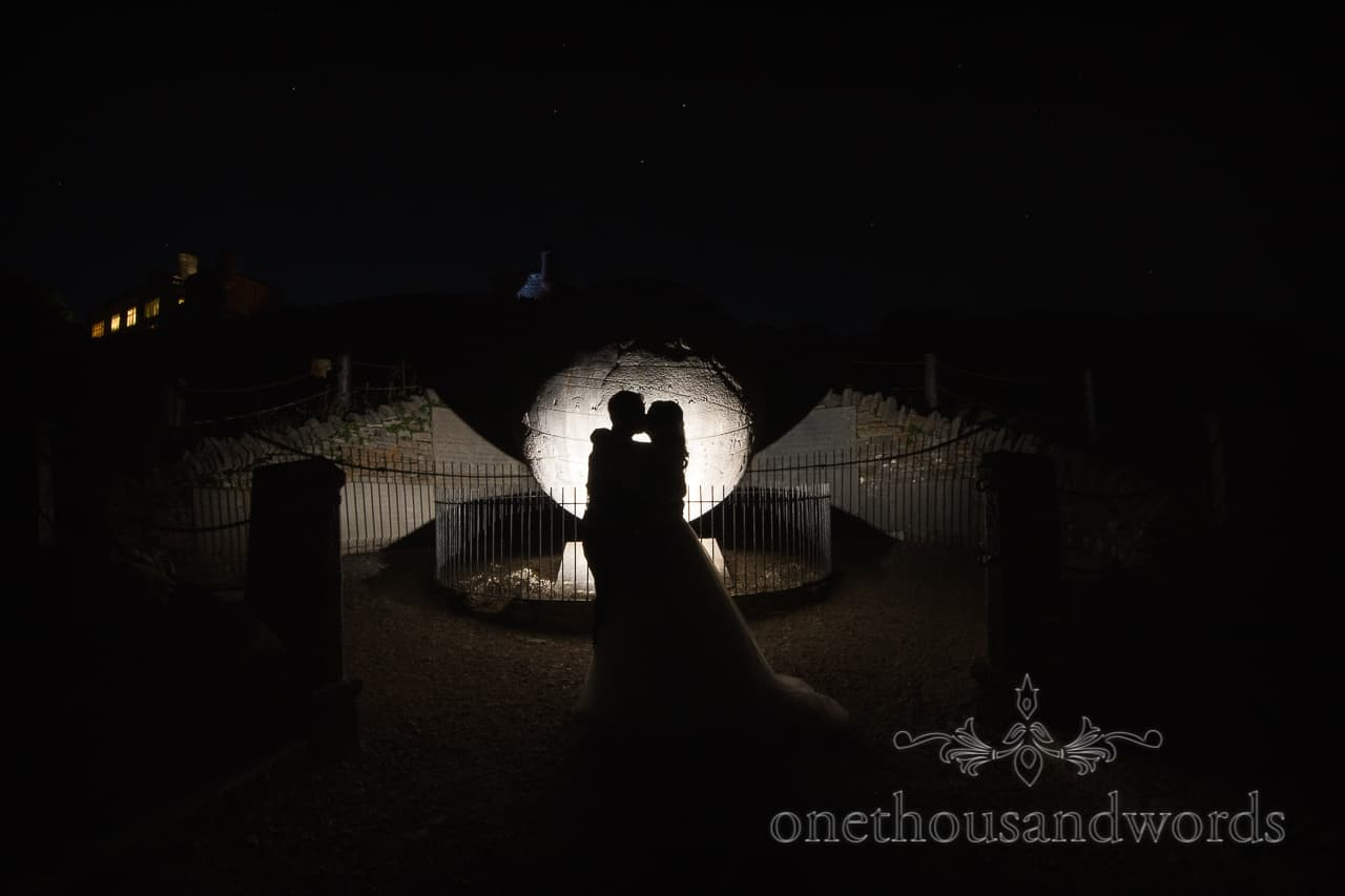 Silhouette of kissing bride and groom with Victorian stone globe at Durlston Castle wedding venue at night with stars