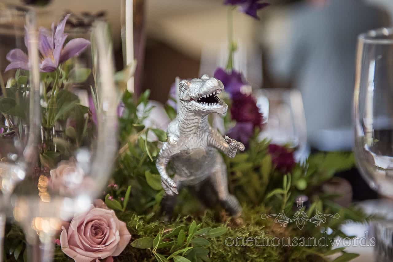 Silver dinosaur themed wedding floral table decoration centre piece detail photograph by one thousand words wedding photographers