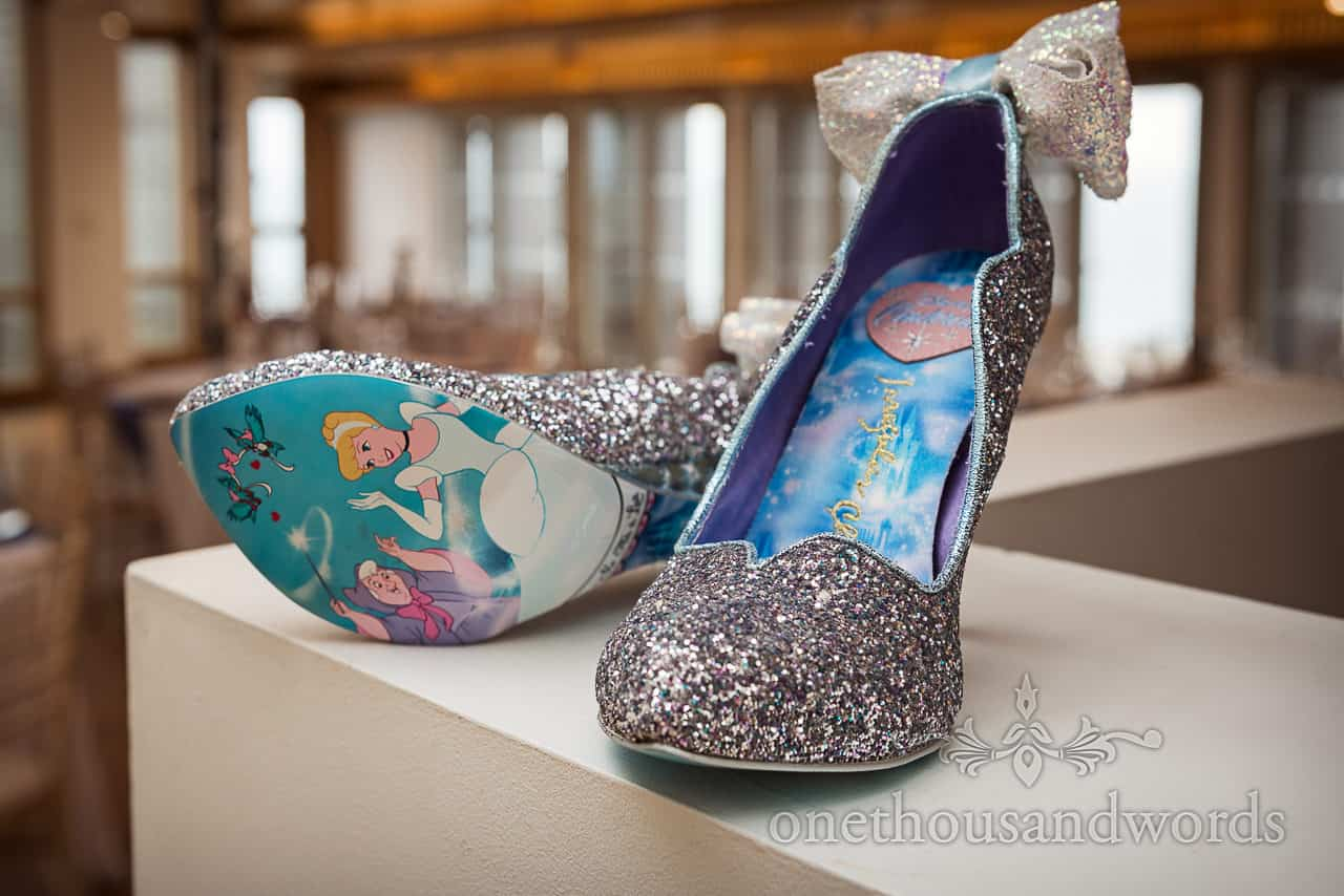 Silver sparkly Disney princess Cinderella wedding shoes with bows detail wedding photograph by one thousand words photography