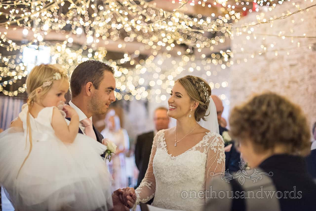 Smiling bride and groom under fairy lit wedding ceremony in Kingston barn venue in Dorset by one thousand words wedding photography