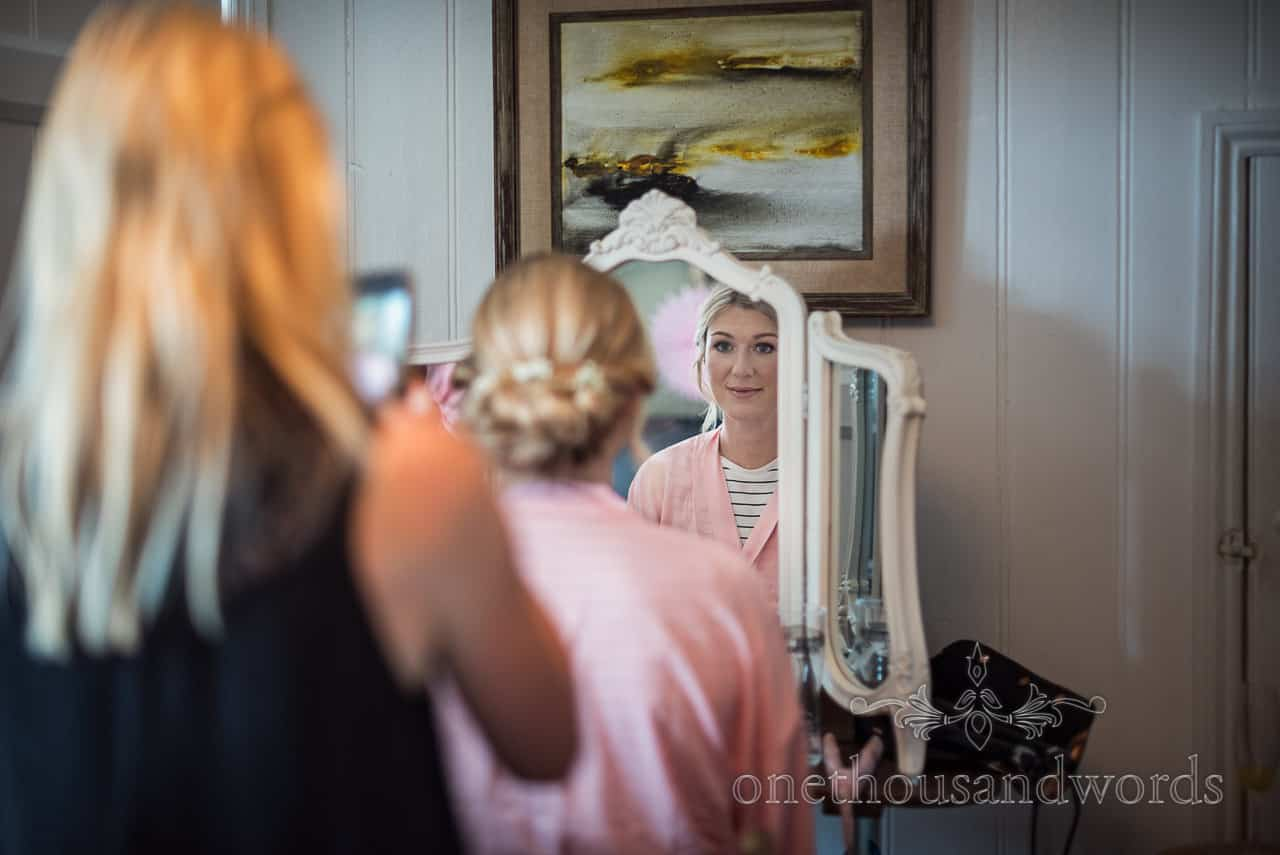 Smiling bridesmaid reflection in mirror as hair stylist takes photo of hair on phone on wedding morning preparations