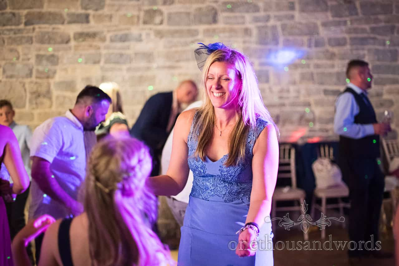 Smiling and dancing guest in blue dress with detailed stitching and blue fascinator under disco lighting during evening reception