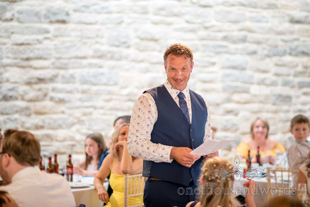 Smiling groom wearing blue waistcoat delivers wedding speech stood amongst guests at Durlston Castle in Dorset