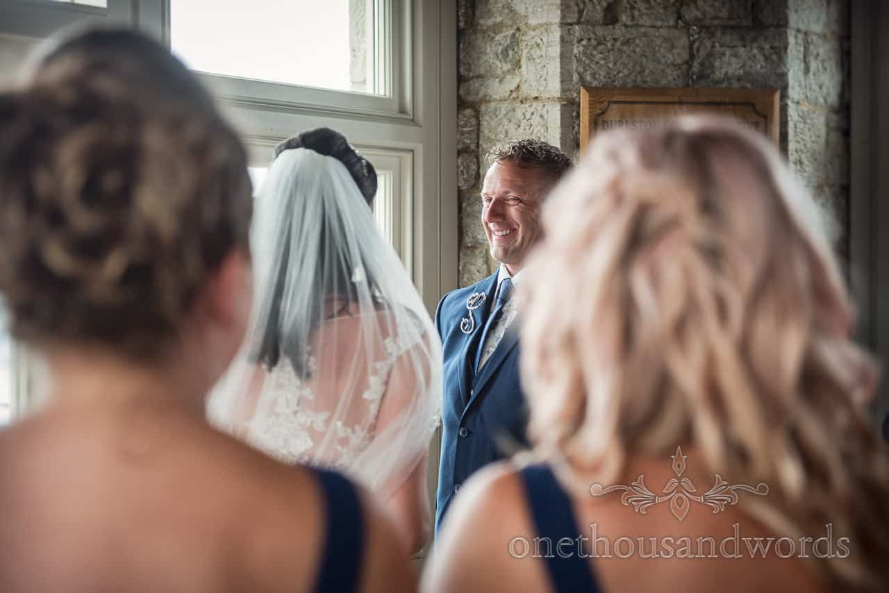 Smiling groom wearing metal sculpted button hole during civil wedding ceremony in Purbeck Dorset castle by one thousand words