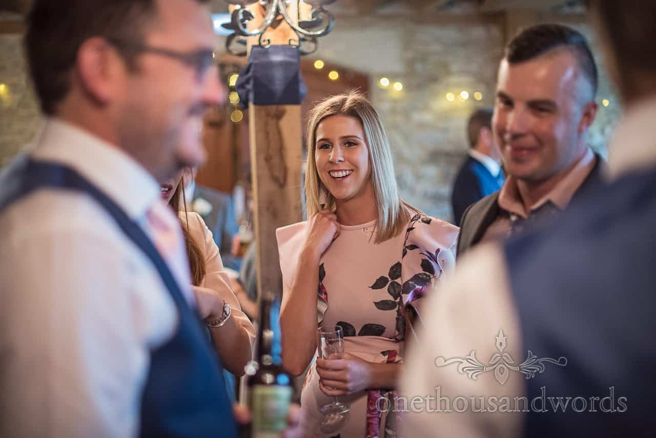 Laughing wedding guest at wedding drinks reception in barn venue in Dorset by one thousand words wedding photography