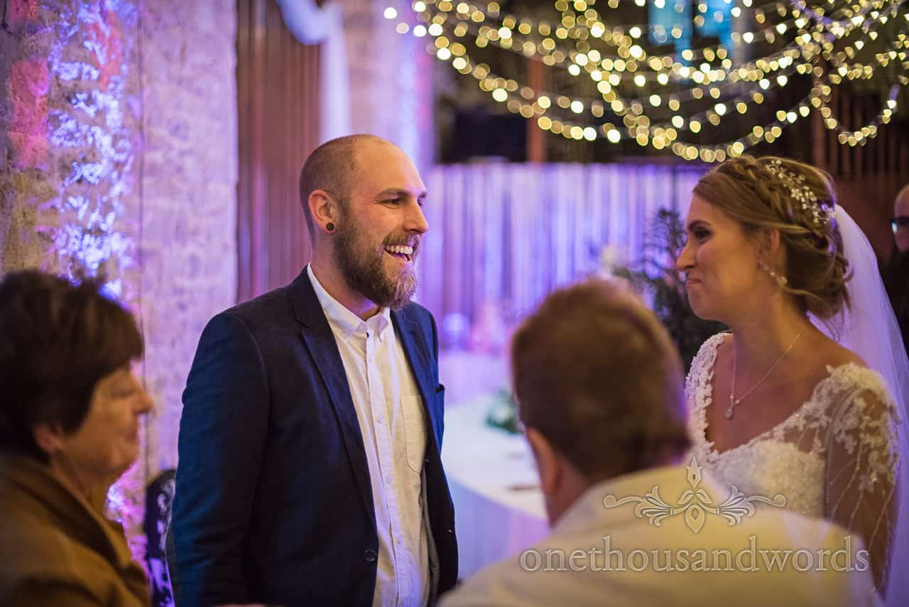 Documentary wedding photograph of smiling wedding guest greeted by bride at Dorset barn wedding evening reception