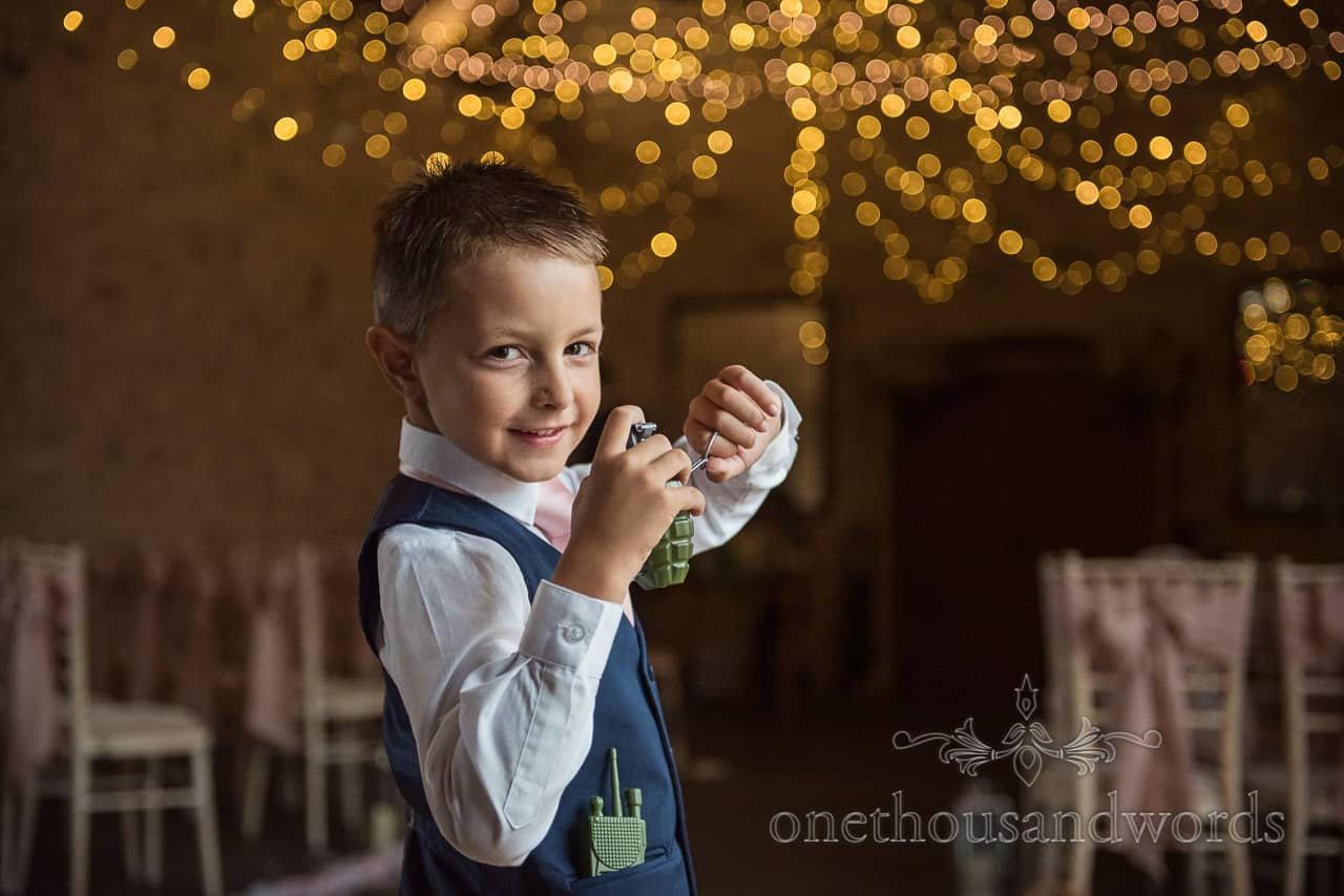 Documentary wedding photograph of bride and groom's son plays with toy hand grenade at barn wedding