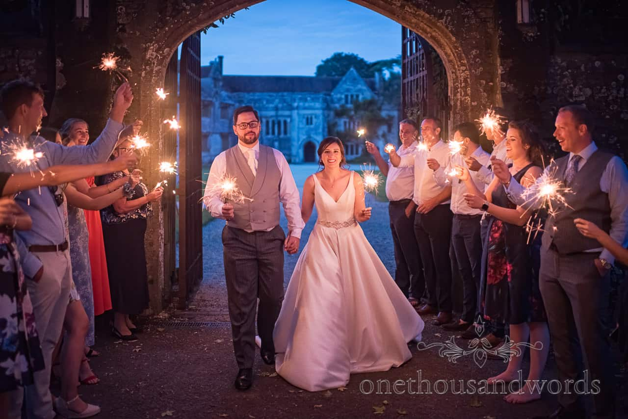 Sparklers photograph of bride and groom with wedding guests at night at Athelhampton House entrance photo by one thousand words