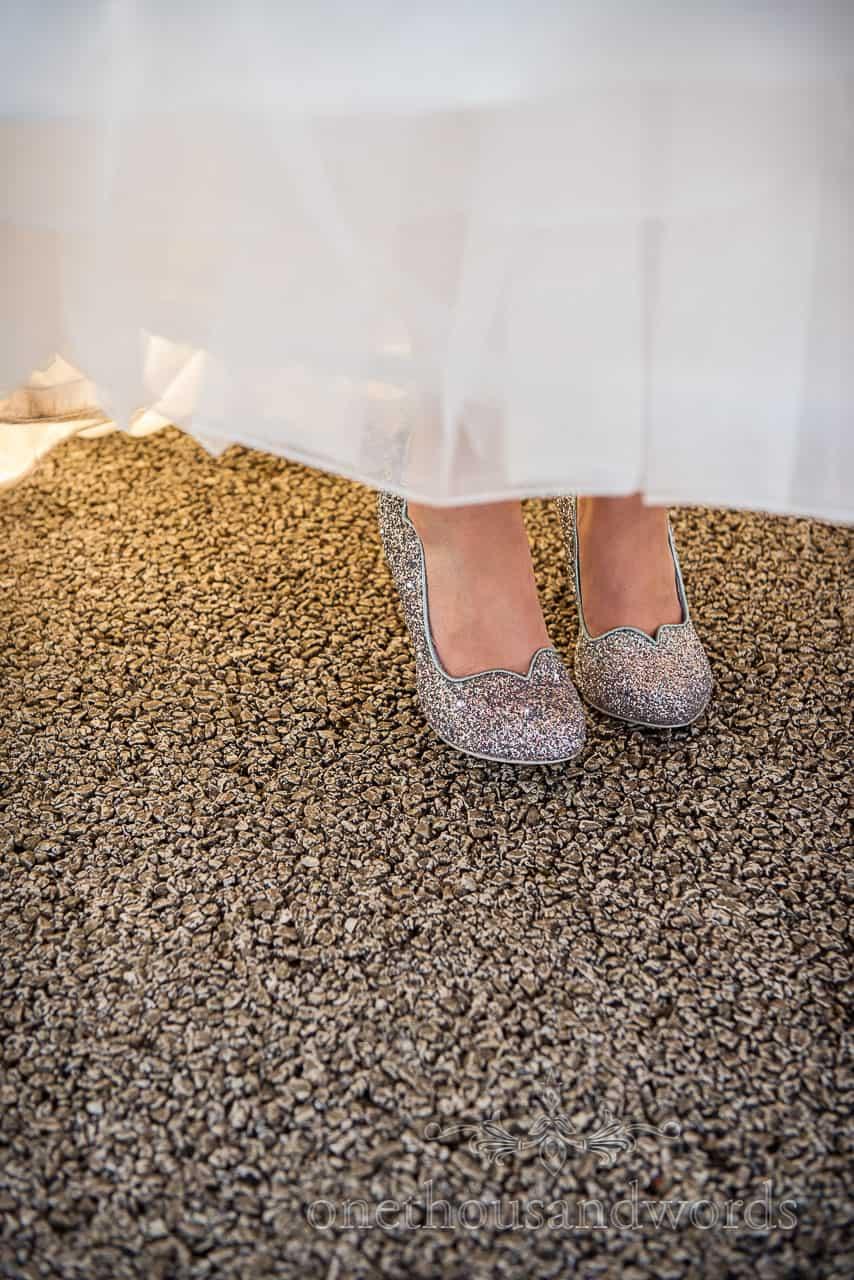 Detail wedding photograph of sparkly silver Irregular Choice designer bridal wedding shoes under white wedding dress