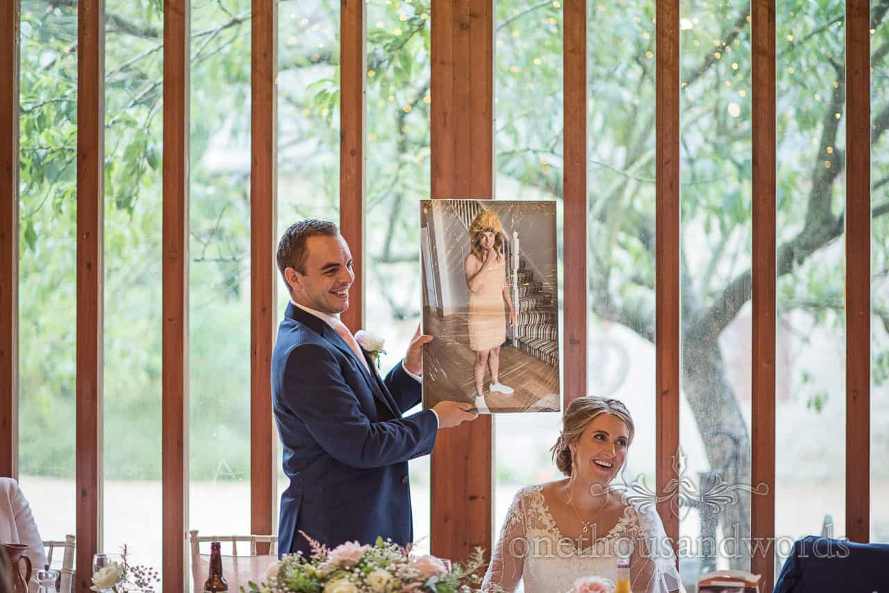 Stag photograph of groom in fancy dress held aloft during wedding speeches as bride adn groom laugh