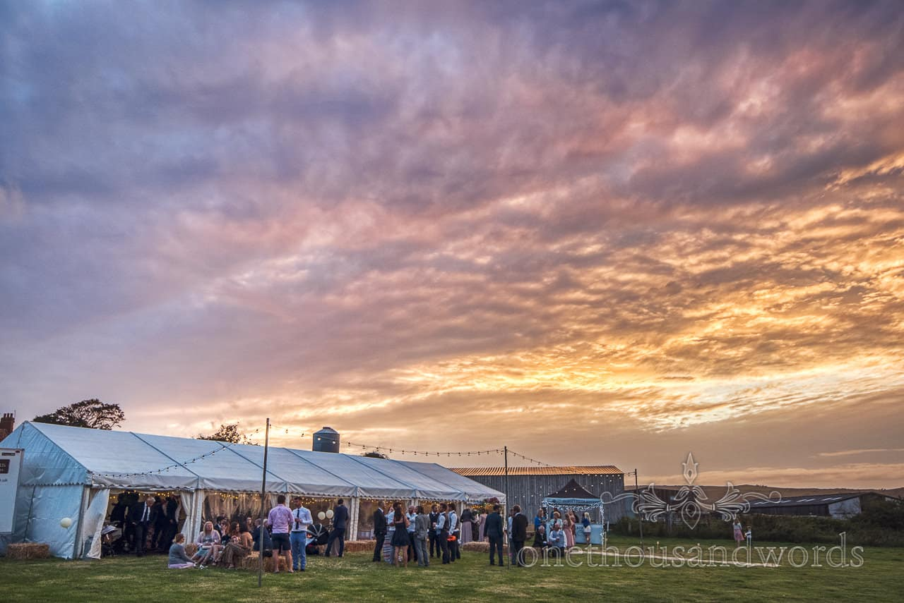 Wedding guests gather under sunset with glowing clouds at Purbeck farm marquee wedding photographs