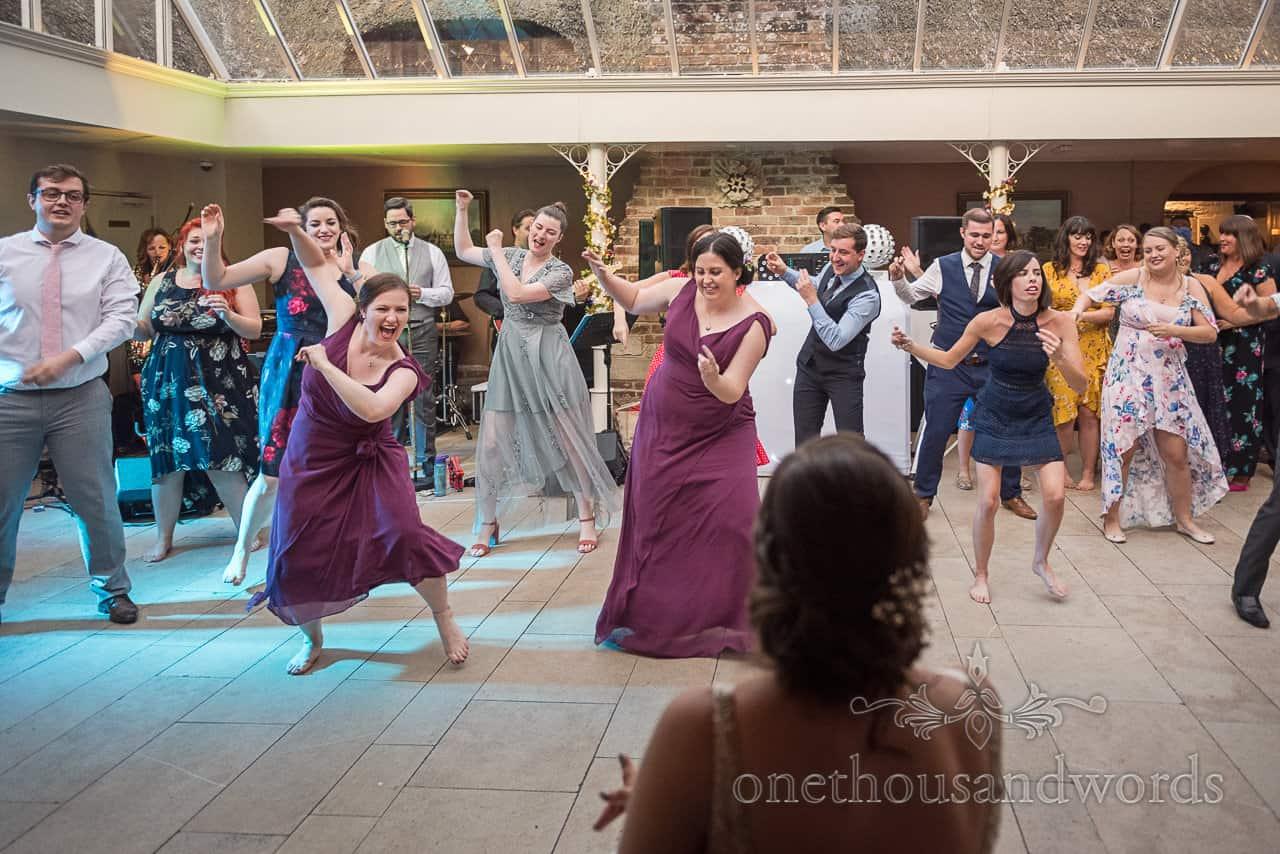 Bride is surprised by dancing wedding guest flash mob at Athelhampton House wedding venue in evening reception by one thousand words