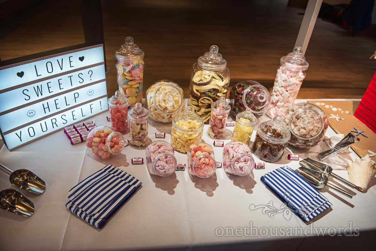 Retro wedding sweet table with jars of favourite sweets, blue striped paper bags and illuminated sign