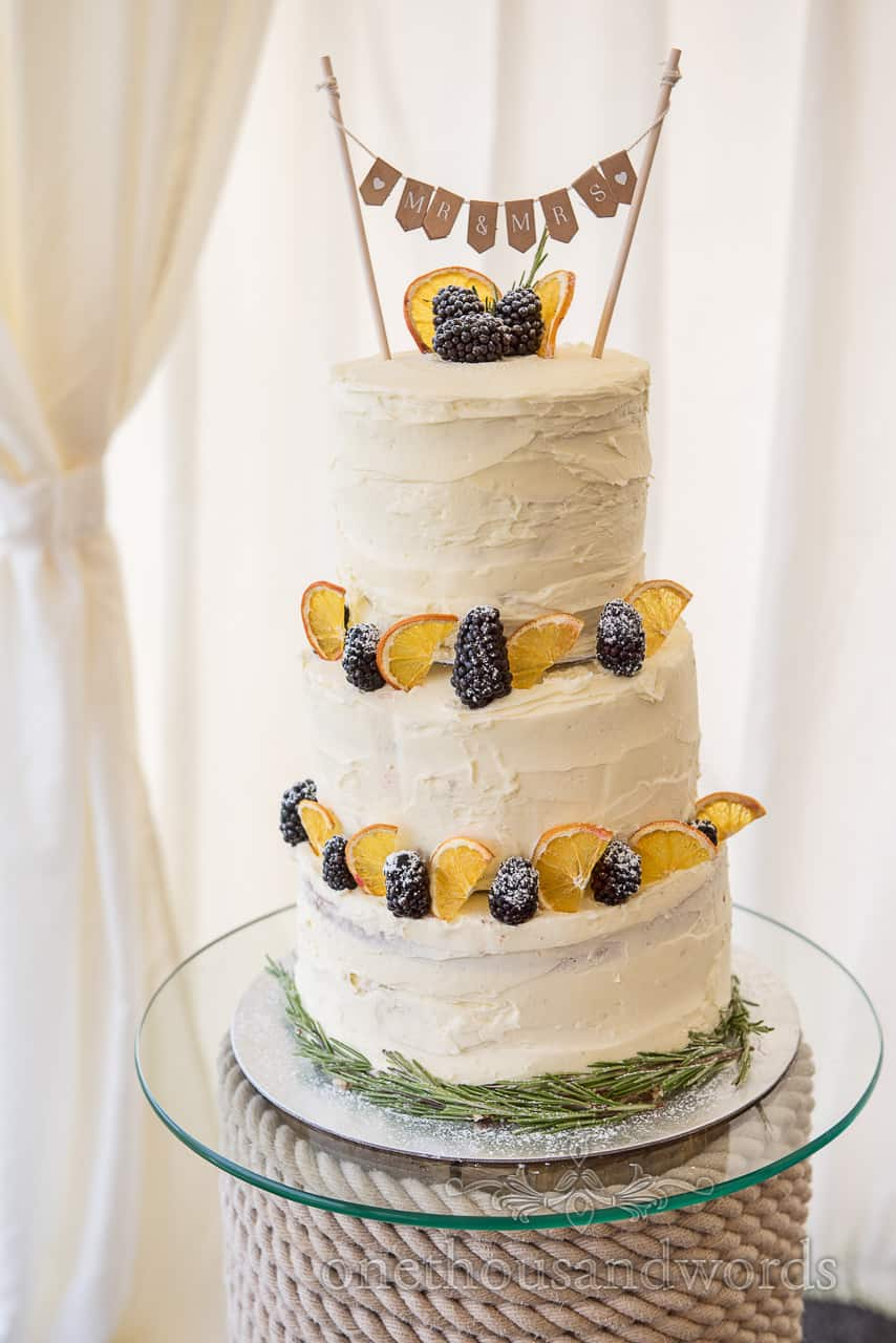 Photograph of three tier white butter iced wedding cake with fruit and Mr & Mrs bunting on glass and rope stand