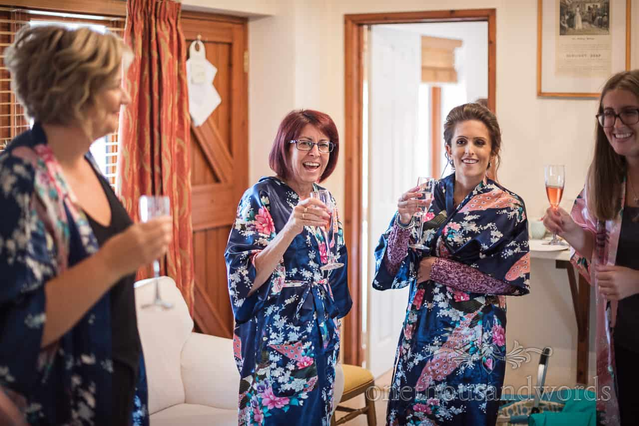 Laughing bridal party in dressing gowns toast during bridal preparations at Dorset wedding by one thousand words photography