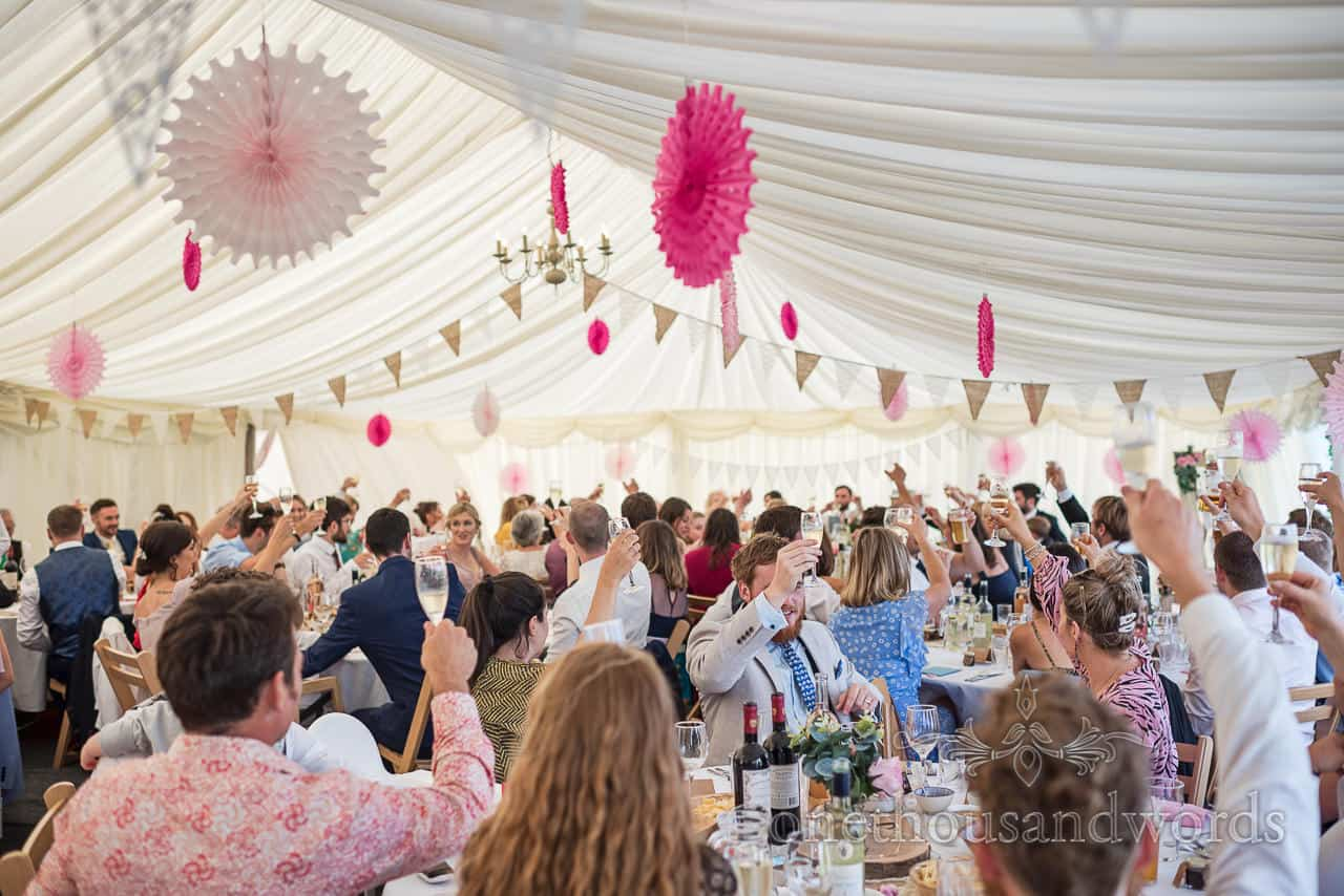 Marquee full of wedding guests raise champagne glasses to toasts at Purbeck farm marquee wedding photographs