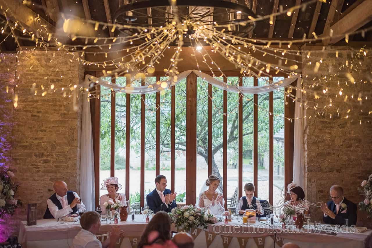 Top table at Kingston Country Courtyard applaud wedding couple's son's speech photograph by one thousand words photography