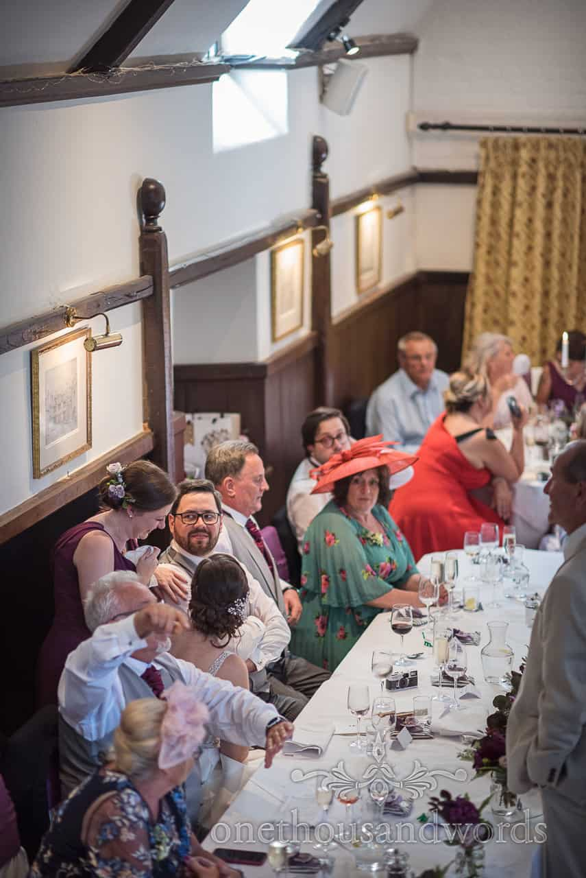 Bridesmaid talks to groom at top table in the long hall decorated for wedding breakfast at Athelhampton House wedding venue