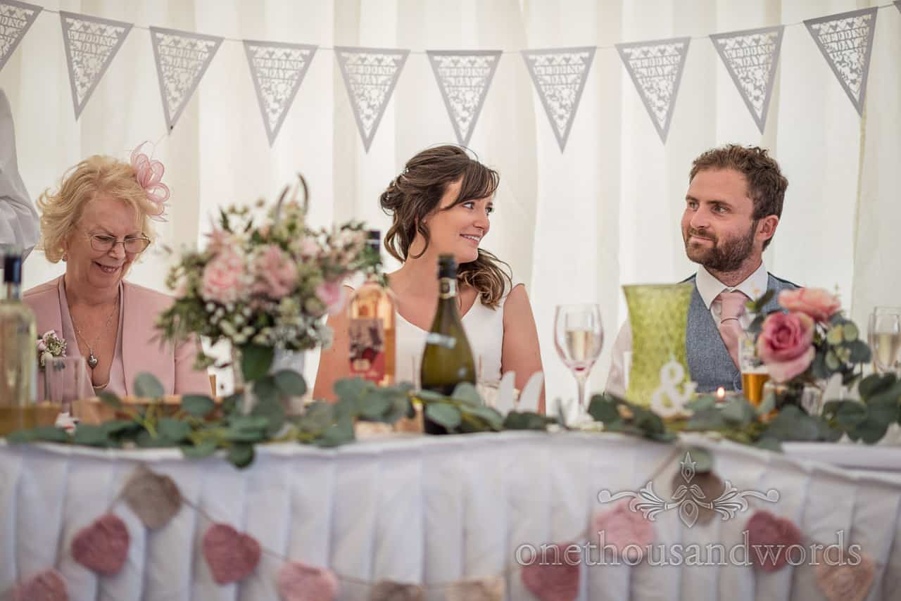 Top table bride and groom reactions in front of marquee bunting during speeches at Purbeck farm marquee wedding photographs