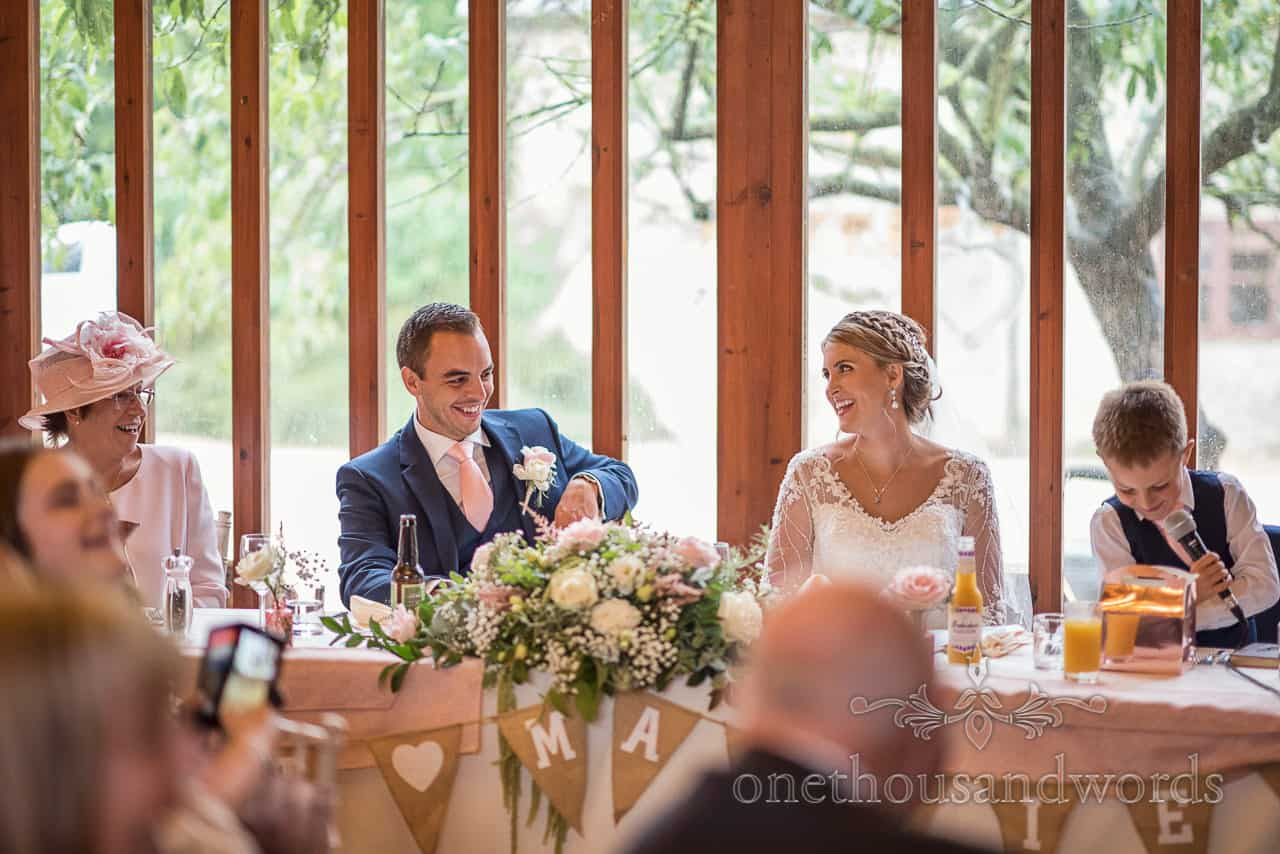Top table's happy reaction photograph to bride and groom's son's wedding speech by one thousand words wedding photography