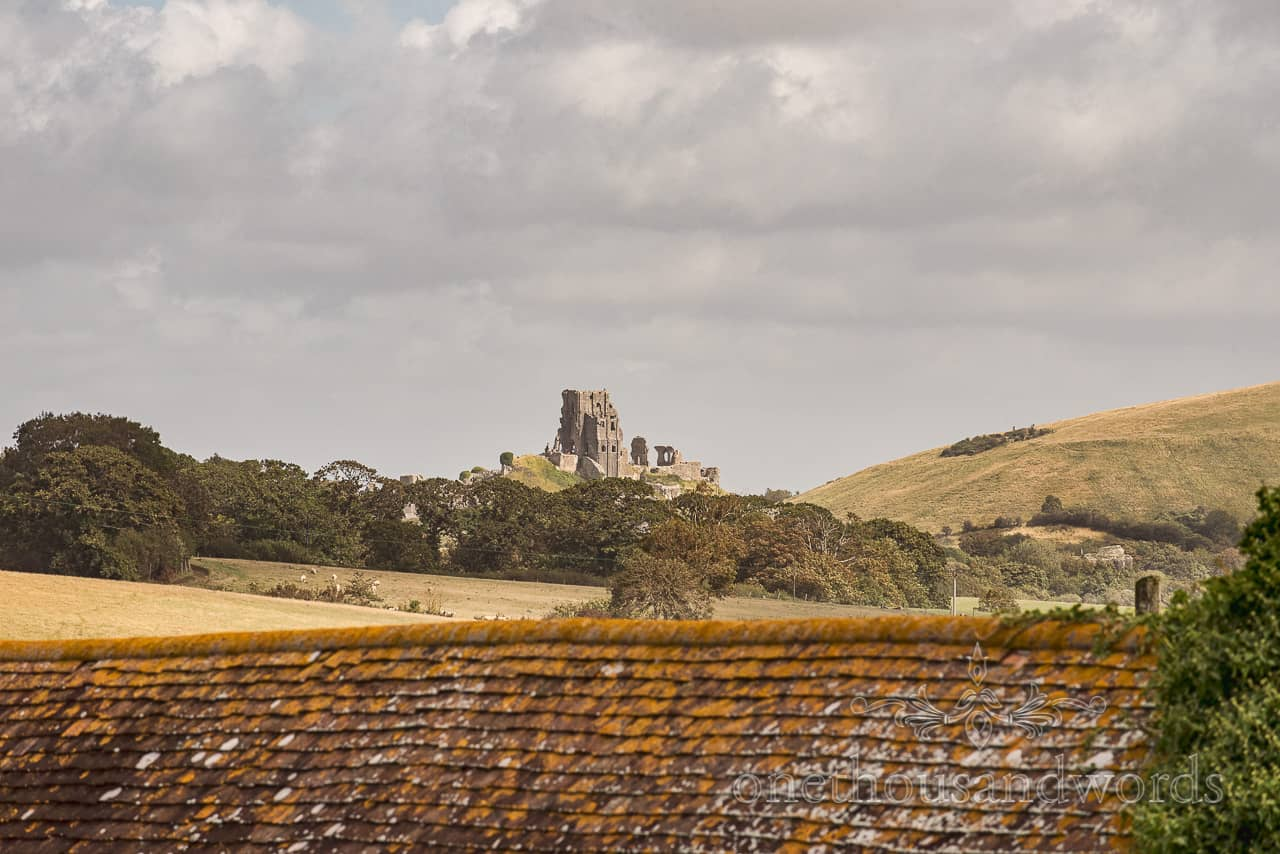View of Corfe Castle in Dorset countryside across tiled barn rooftop taken from grooms wedding morning preparation venue