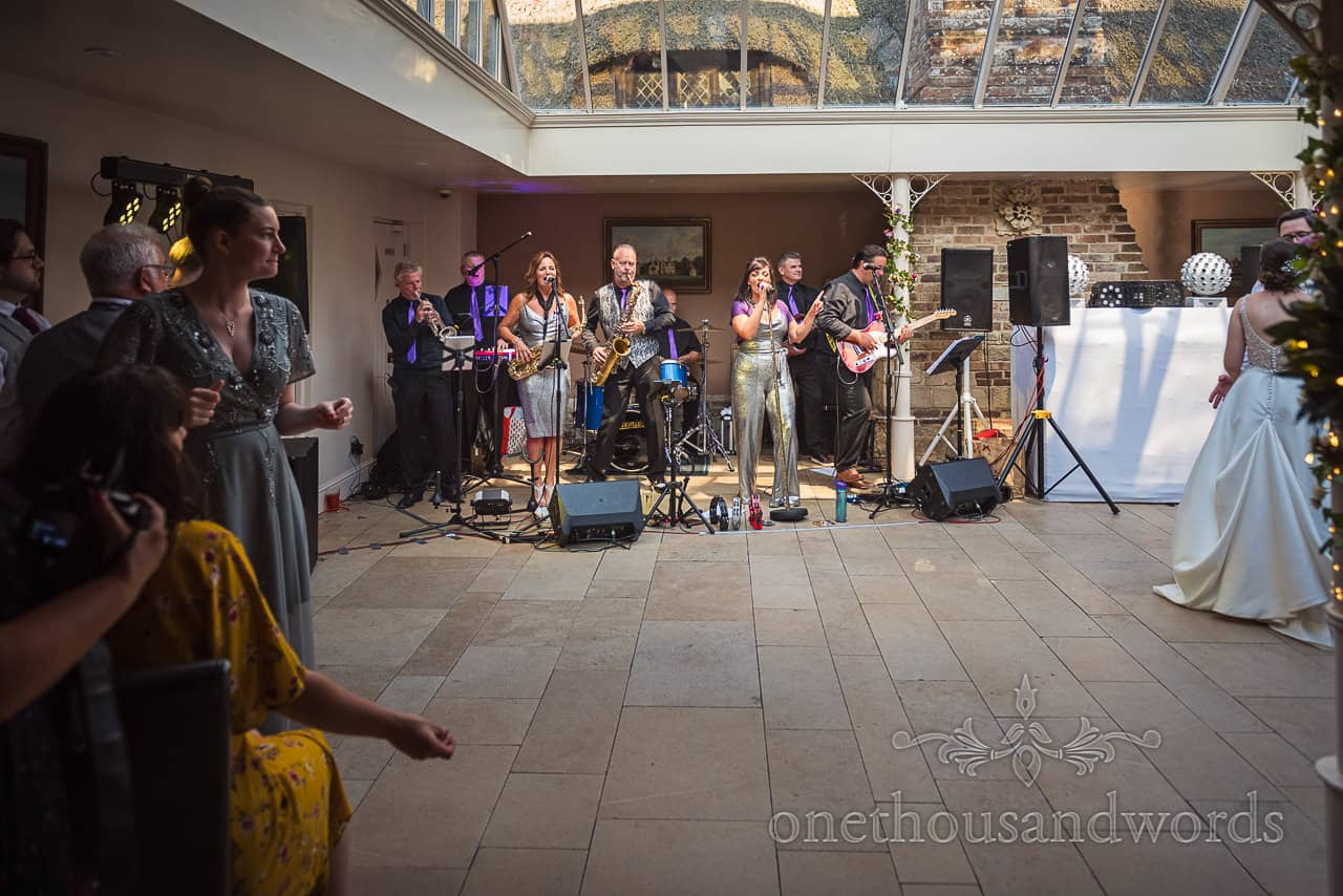 Wedding band play evening reception in The Coach House at Athelhampton House wedding venue in Dorset by one thousand words