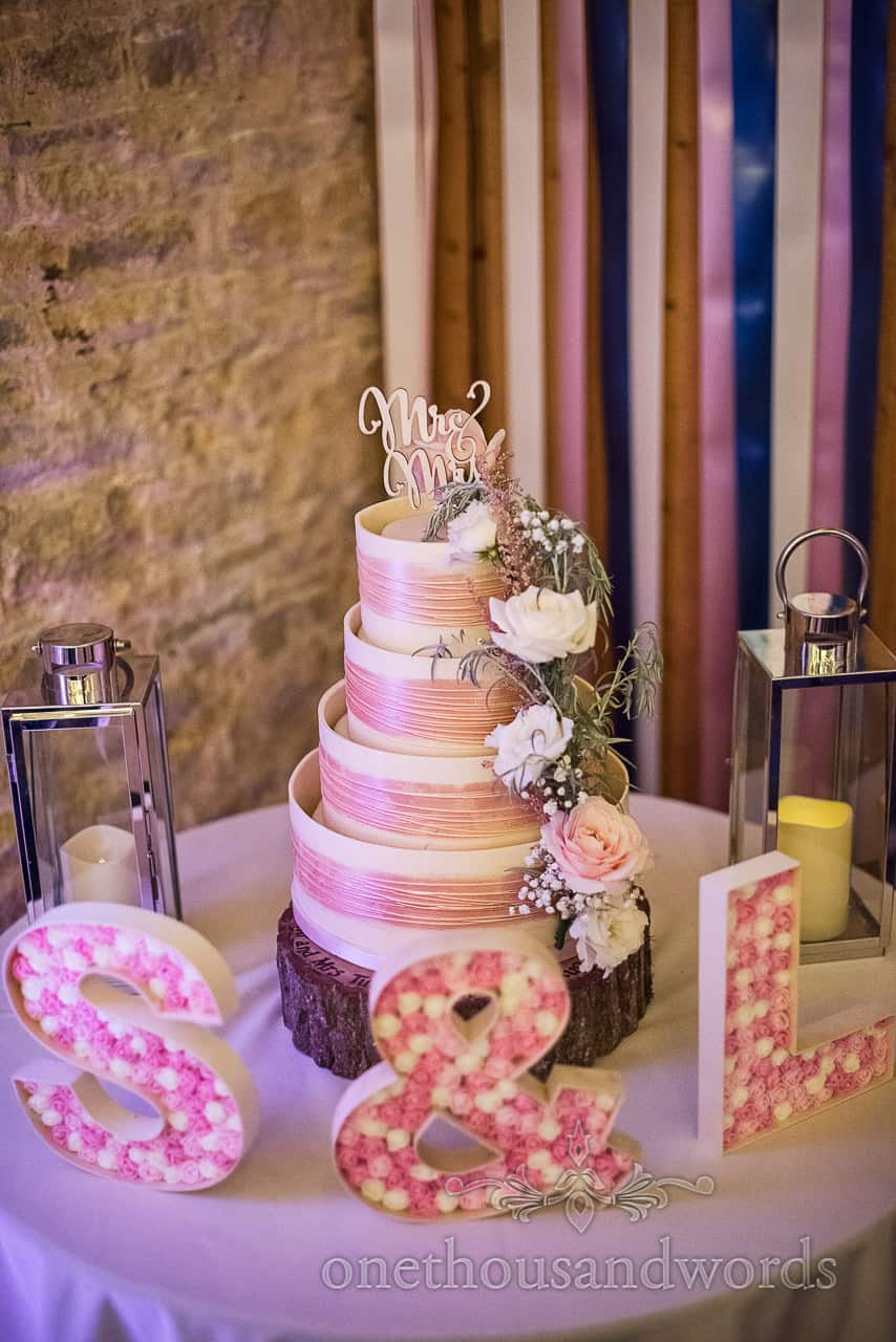 Four tier white and pink chocolate wedding cake on log slice decorated with flowers and candle lanterns by one thousand words