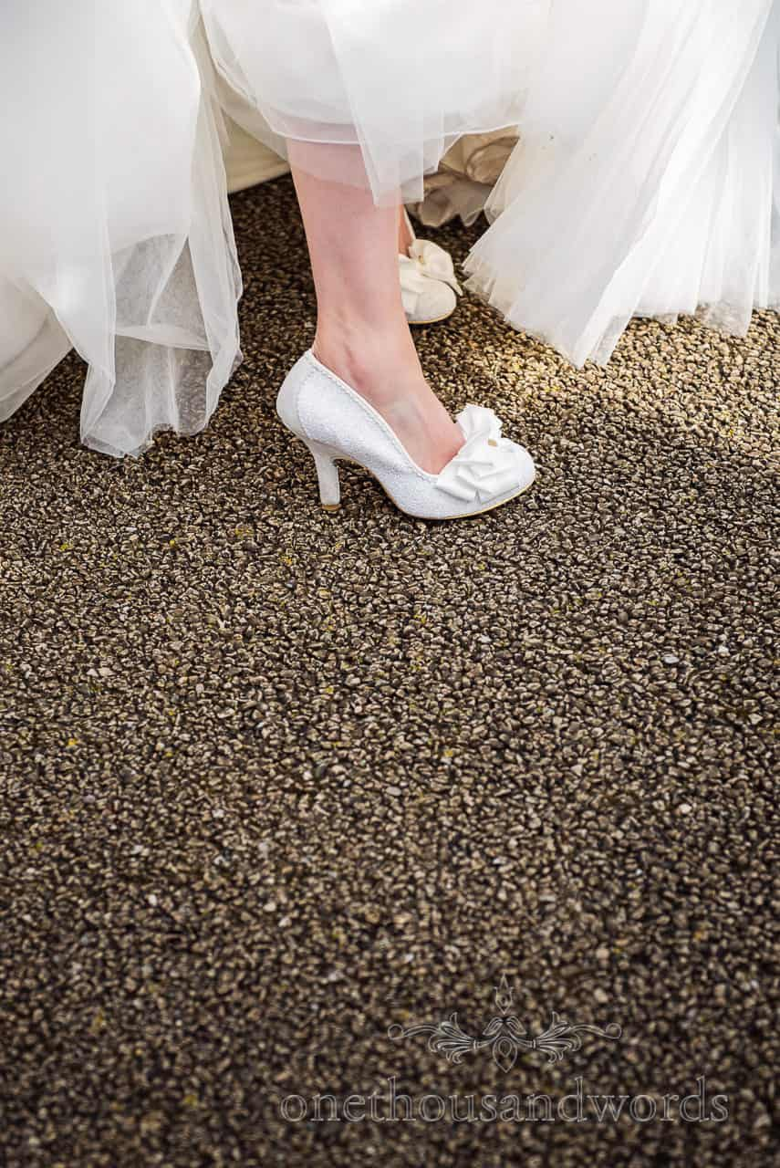 Wedding detail photograph of Irregular Choice white designer wedding shoes with sparkles, heels and white lace bows