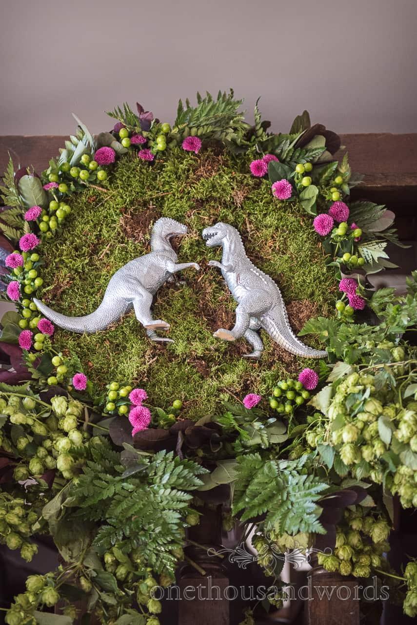 Wedding detail photograph of silver dinosaurs in moss flower green foliage dinosaur themed centre piece wedding decoration