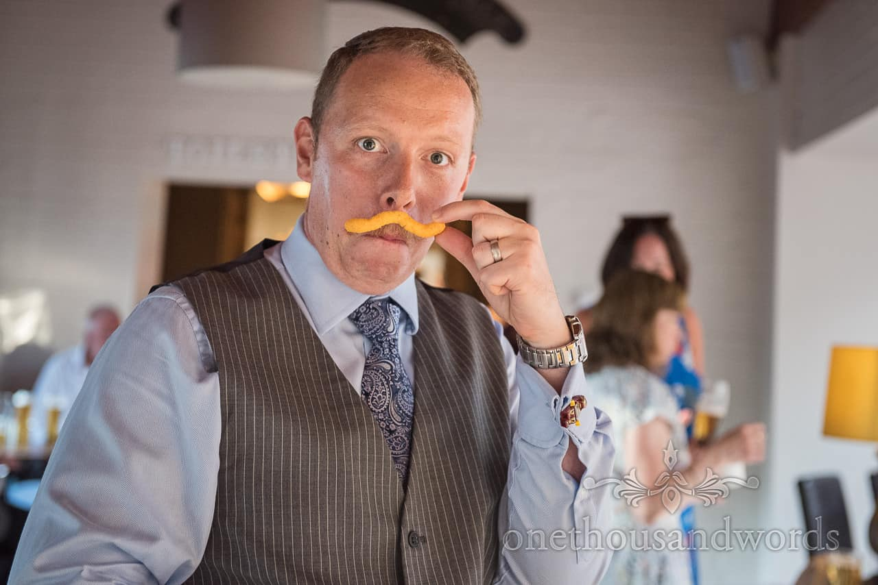 Funny wedding guest in grey striped waistcoat holds up a cheesy crisp moustache during wedding evening reception photo