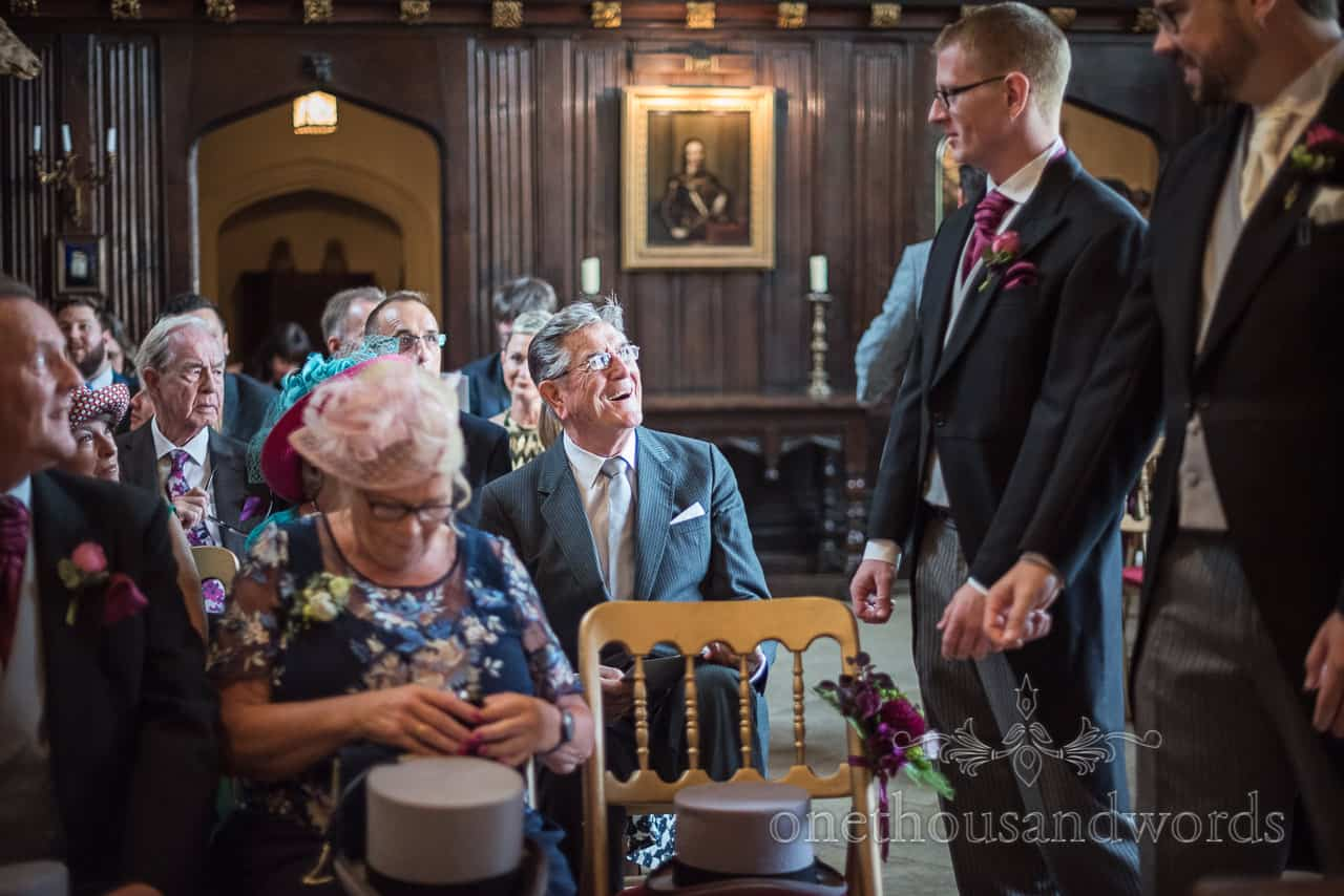 Documentary photograph of wedding guest laughing in grand hall with groomsmen before wedding ceremony by one thousand words